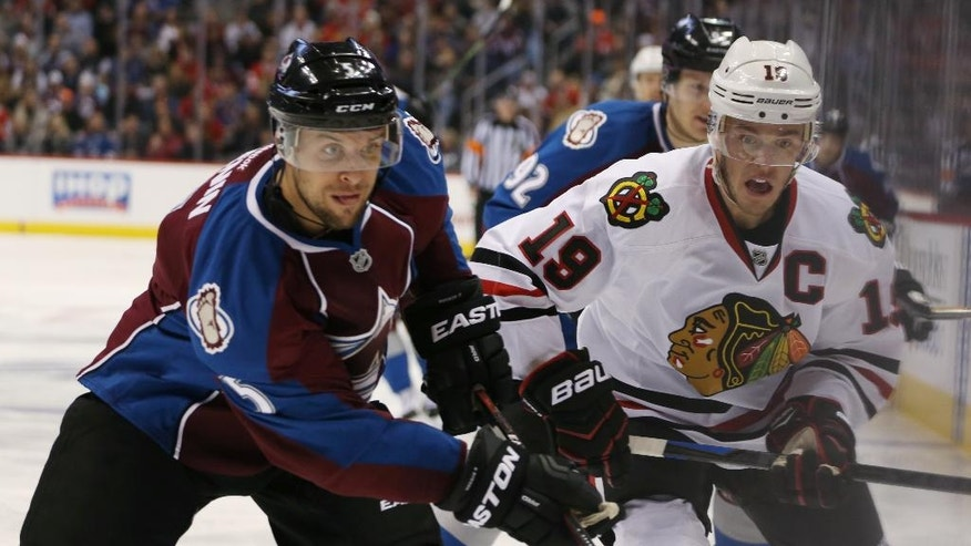 Colorado Avalanche defenseman Nate Guenin, left, pursues loose puck with Chicago Blackhawks center Jonathan Toews in the second period of an NHL hockey game in Denver on Wednesday, Nov. 26, 2014. (AP Photo/David Zalubowski)