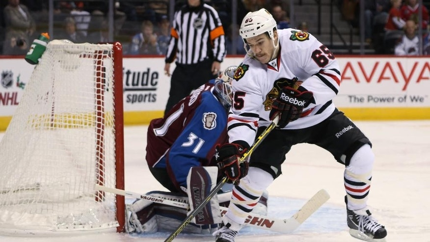 Chicago Blackhawks center Andrew Shaw, front, tries to corral the puck in front of the net as Colorado Avalanche goalie Calvin Pickard looks on in the second period of an NHL hockey game in Denver on Wednesday, Nov. 26, 2014. (AP Photo/David Zalubowski)