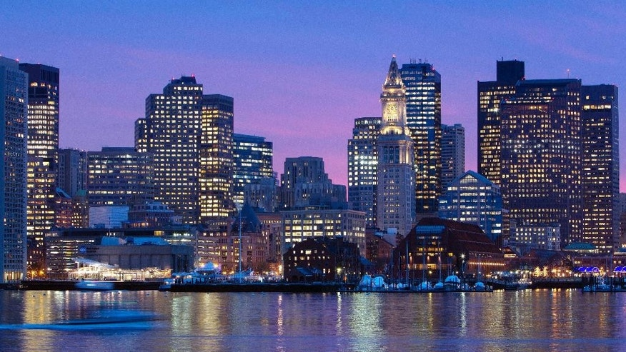 FILE - In this Jan. 6, 2012 file photo, the Boston city skyline is illuminated at dusk as it reflects off the waters of Boston Harbor. The city is bidding on the 2024 Summer Olympics, and the crux of the proposal is a walkable, sustainable, technology-based event that would harness the resources of the area's 100 colleges and universities to keep the Games affordable and compact. (AP Photo/Michael Dwyer, File)