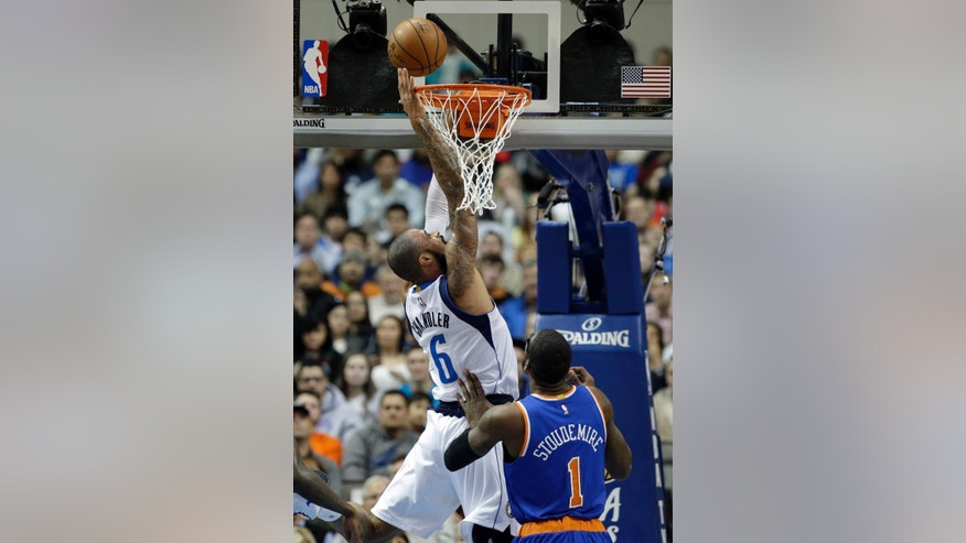 Dallas Mavericks center Tyson Chandler (6) goes up to tap in the ball for a basket over New York Knicks' Amare Stoudemire (1) in the first half of an NBA basketball game, Wednesday, Nov. 26, 2014, in Dallas. (AP Photo/Tony Gutierrez)