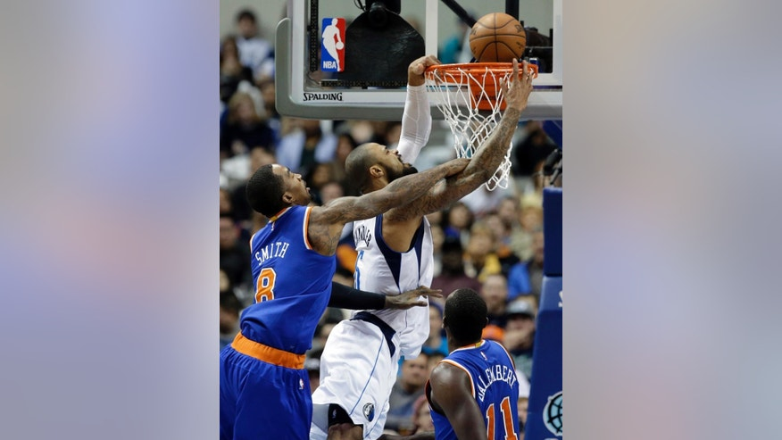 New York Knicks guard J.R. Smith (8) is unable to stop Dallas Mavericks' Tyson Chandler from making a basket as center Samuel Dalembert (11), of Haiti, watches in the first half of an NBA basketball game, Wednesday, Nov. 26, 2014, in Dallas. (AP Photo/Tony Gutierrez)