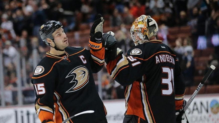 Anaheim Ducks' Ryan Getzlaf, left, and goalie Frederik Andersen, of Denmark, celebrate their team's 3-2 win against the Calgary Flames in an NHL hockey game Tuesday, Nov. 25, 2014, in Anaheim, Calif. (AP Photo/Jae C. Hong)