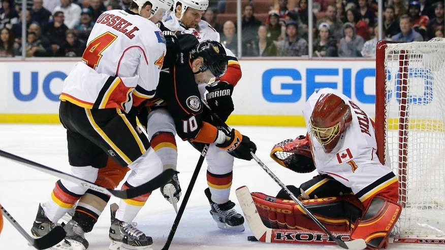 Anaheim Ducks' Corey Perry(10) is defended by Calgary Flames' Kris Russell(4) and Dennis Wideman(6) as he tries to score against goalie Jonas Hiller (1) during the second period of an NHL hockey game Tuesday, Nov. 25, 2014, in Anaheim, Calif. (AP Photo/Jae C. Hong)