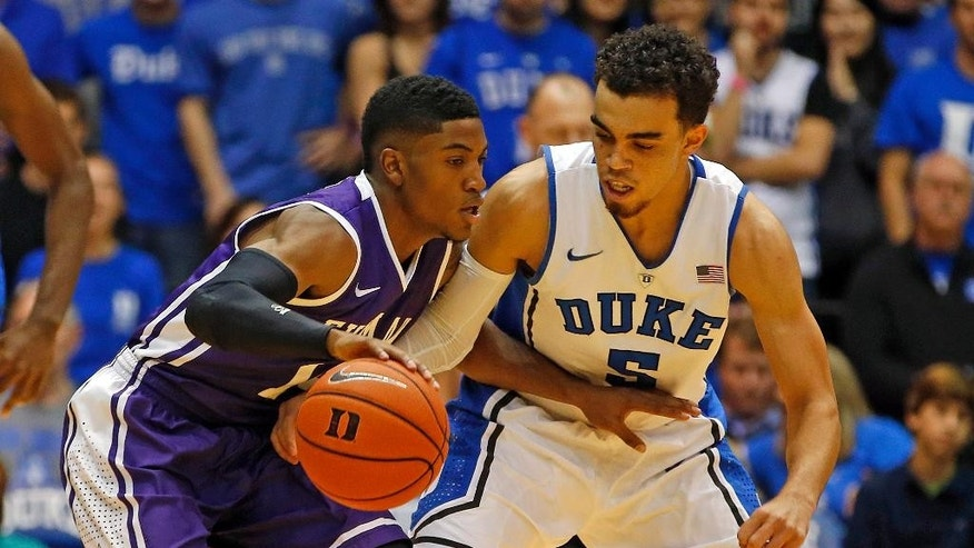 Duke's Tyus Jones (5) reaches in for the ball on Furman's Stephen Croone (14) during the first half of an NCAA college basketball game in Durham, N.C., Wednesday, Nov. 26, 2014. (AP Photo/Karl B DeBlaker)