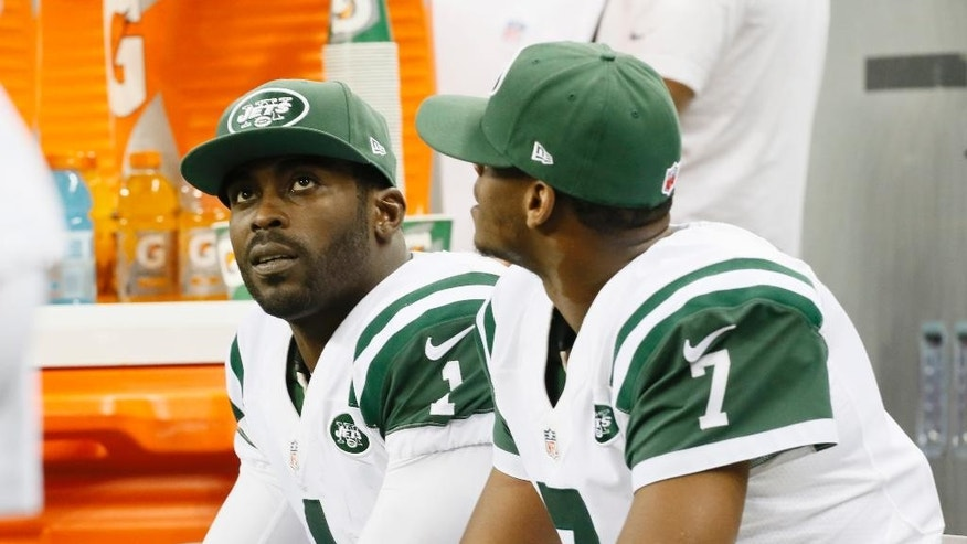 New York Jets quarterbacks Michael Vick (1) and Geno Smith (7) are seen on the bench during the second half of an NFL football game against the Buffalo Bills in Detroit, Monday, Nov.24, 2014. (AP Photo/Paul Sancya)