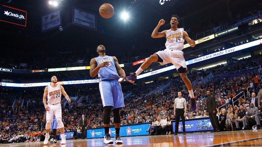 Phoenix Suns' Gerald Green (14) yells and pumps his fist as he celebrates his dunk over Denver Nuggets' Darrell Arthur, middle, as Suns' Miles Plumlee (22) looks on during the second half of an NBA basketball game Wednesday, Nov. 26, 2014, in Phoenix.  The Suns defeated the Nuggets 120-112. (AP Photo/Ross D. Franklin)