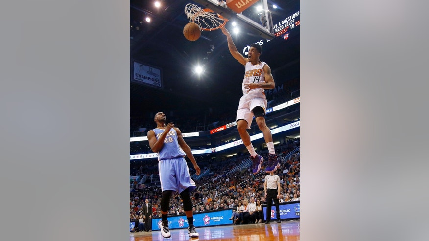 Phoenix Suns' Gerald Green (14) shouts as he dunks as Denver Nuggets' Darrell Arthur (00) looks on during the second half of an NBA basketball game Wednesday, Nov. 26, 2014, in Phoenix.  The Suns defeated the Nuggets 120-112. (AP Photo/Ross D. Franklin)