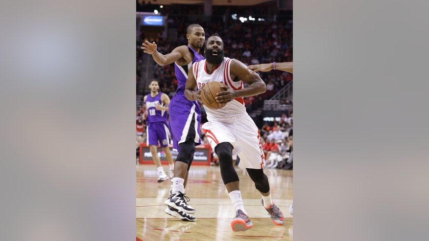 Houston Rockets' James Harden, right, passes Sacramento Kings' Ramon Sessions on his way to the basket in the second half of an NBA basketball game Wednesday, Nov. 26, 2014, in Houston. The Rockets won 102-89. (AP Photo/Pat Sullivan)