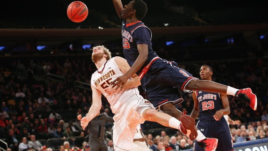 St. John's guard Sir'Dominic Pointer (15) scores over Minnesota center Elliott Eliason (55) in the second half of an NCAA college basketball game at Madison Square Garden in New York, Wednesday, Nov. 26, 2014. (AP Photo/Kathy Willens)