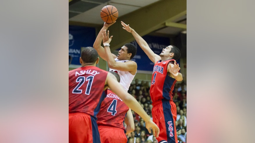 San Diego State guard Trey Kell, top center, shoots the basketball while being defended by Arizona forward Brandon Ashley (21),  guard T.J. McConnell (4) and guard Elliott Pitts, right, in the first half of an NCAA college basketball game at the Maui Invitational on Wednesday, Nov. 26, 2014, in Lahaina, Hawaii. (AP Photo/Eugene Tanner)