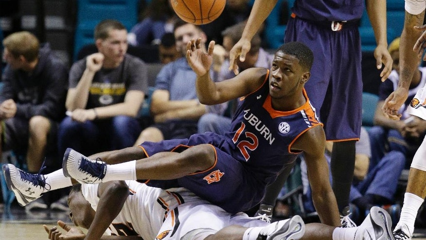 Auburn's K.C. Ross-Miller (12) falls on Oregon State's Jarmal Reid during the second half of an NCAA college basketball game Wednesday, Nov. 26, 2014, in Las Vegas. (AP Photo/John Locher)