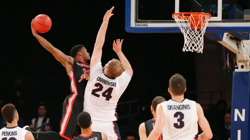 Georgia guard Kenny Gaines (12) passes around the defense of Gonzaga center Przemek Karnowski (24) with Gonzaga guard Kyle Dranginis (3) looking on in the first half of an NCAA college basketball game in New York, Wednesday, Nov. 26, 2014. (AP Photo/Kathy Willens)