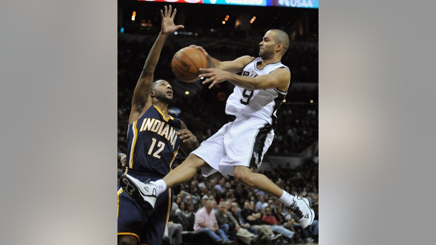 San Antonio Spurs guard Tony Parker, right, of France, passes around Indiana Pacers guard A.J. Price during the first half of an NBA basketball game, Wednesday, Nov. 26, 2014, in San Antonio. (AP Photo/Darren Abate)