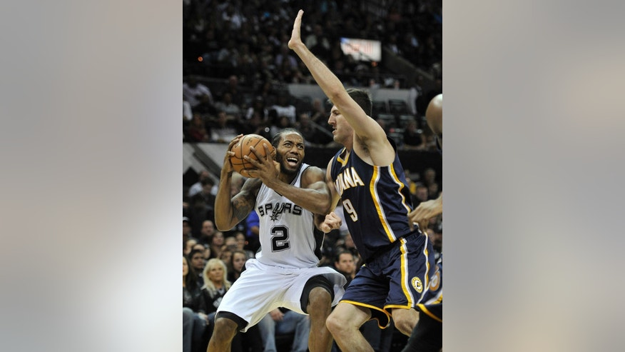 San Antonio Spurs forward Kawhi Leonard, left, drives around Indiana Pacers forward Damjan Rudez, of Croatia, during the first half of an NBA basketball game, Wednesday, Nov. 26, 2014, in San Antonio. (AP Photo/Darren Abate)