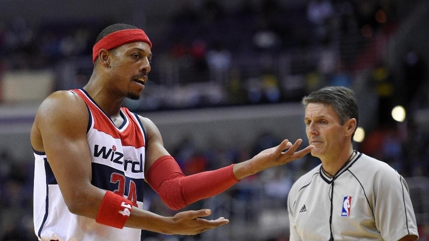 Washington Wizards forward Paul Pierce (34) gestures next to referee Scott Foster, right, after he was called for a foul during the second half of an NBA basketball game, Tuesday, Nov. 25, 2014, in Washington. The Hawks won 106-102.(AP Photo/Nick Wass)