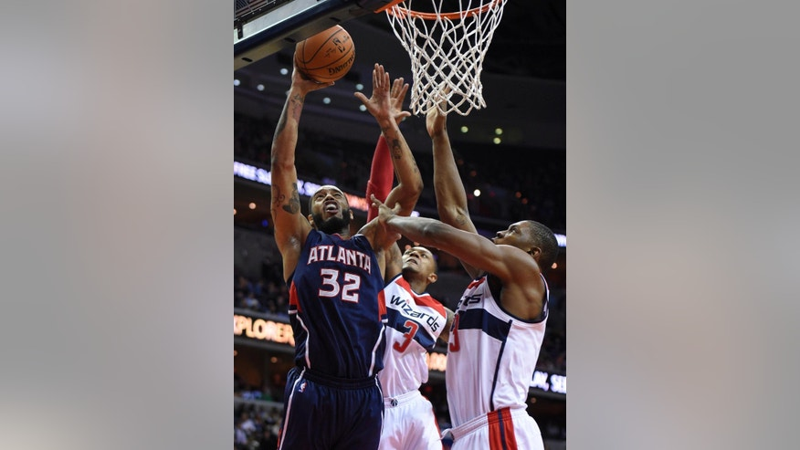Atlanta Hawks forward Mike Scott (32) goes to the basket against Washington Wizards guard Bradley Beal (3) and Kevin Seraphin, right, of France, during the second half of an NBA basketball game, Tuesday, Nov. 25, 2014, in Washington. The Hawks won 106-102.(AP Photo/Nick Wass)