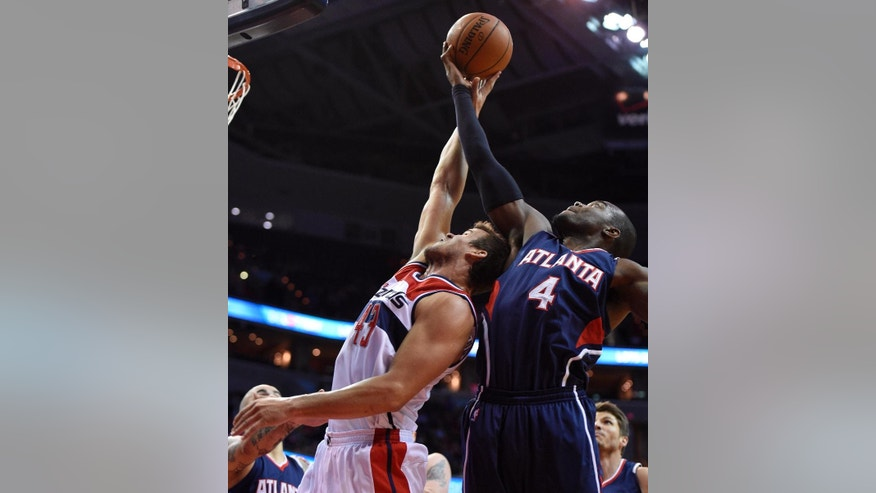 Atlanta Hawks forward Paul Millsap (4) battles for the ball against Washington Wizards forward Kris Humphries, left, during the first half of an NBA basketball game, Tuesday, Nov. 25, 2014, in Washington. (AP Photo/Nick Wass)