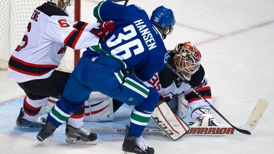 New Jersey Devils defenseman Andy Greene (6) tries to clear Vancouver Canucks right wing Jannik Hansen (36) from in front of New Jersey Devils goalie Cory Schneider (35) during the third period of an NHL hockey game, Tuesday, Nov. 25, 2014 in Vancouver, British Columbia.  (AP Photo/The Canadian Press, Jonathan Hayward)