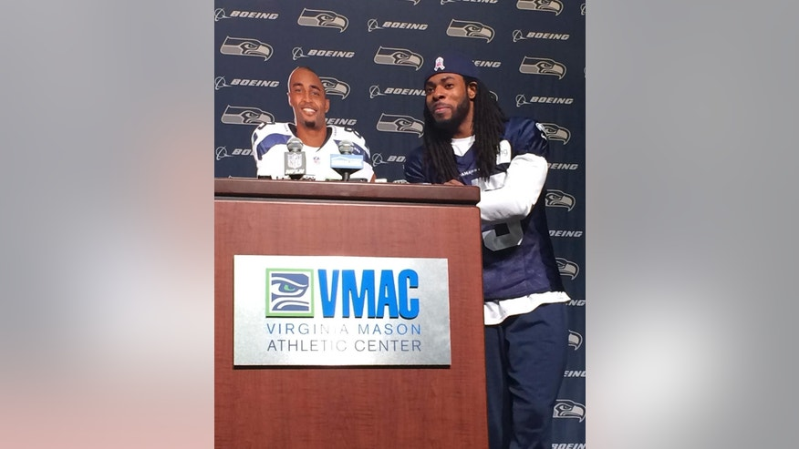 Seattle Seahawks cornerback Richard Sherman, right, stands beside a cardboard cutout of wide receiver Doug Baldwin, at podium, while speaking at the Seahawks headquarters Tuesday, Nov.25, 2014, in Renton, Wash. Baldwin himself was hiding behind the cardboard cutout. The pair put together a routine that took digs at the NFL after teammate Marshawn Lynch was fined $100,000 by the league last week for not speaking to the media. (AP Photo/Tim Booth)