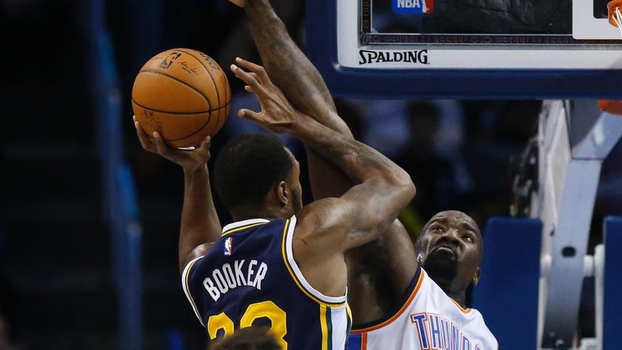 Oklahoma City Thunder center Kendrick Perkins, right, blocks a shot by Utah Jazz forward Trevor Booker, left, in the second quarter of an NBA basketball game in Oklahoma City, Wednesday, Nov. 26, 2014. (AP Photo/Sue Ogrocki)