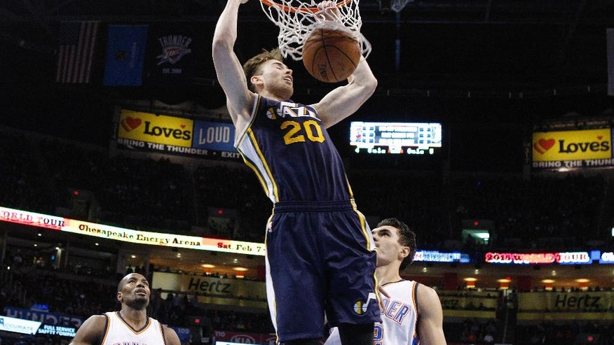 Utah Jazz forward Gordon Hayward (20) dunks in front of Oklahoma City Thunder forward Serge Ibaka (9) and center Steven Adams, right, in the first quarter of an NBA basketball game in Oklahoma City, Wednesday, Nov. 26, 2014. (AP Photo/Sue Ogrocki)