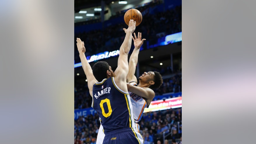 Oklahoma City Thunder's Jeremy Lamb, right, shoots as Utah Jazz's Enes Kanter (0) defends in the second quarter of an NBA basketball game in Oklahoma City, Wednesday, Nov. 26, 2014. (AP Photo/Sue Ogrocki)