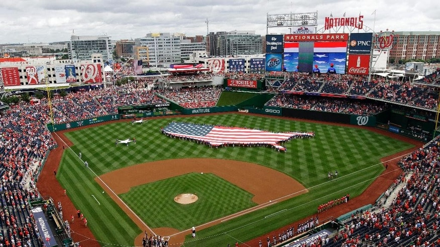 FILE - This July 4, 2013, file photo shows a U.S. flag, in the shape of the country, in the outfield before a baseball game between the Washington Nationals and the Milwaukee Brewers at Nationals Park in Washington. The city of political polarization is hoping an Olympic bid can bring everyone together. (AP Photo/Mark Tenally, File)
