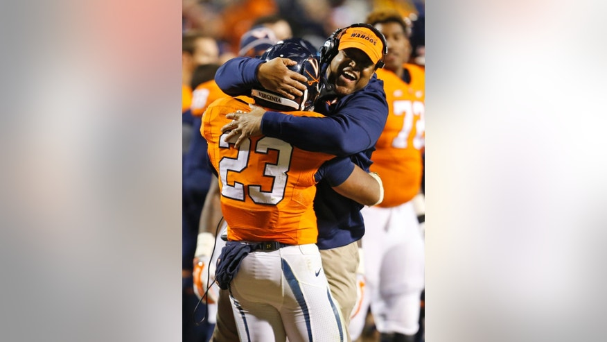 Virginia head coach Mike London, right, hugs Virginia running back Khalek Shepherd (23) after a touchdown during the second half of an NCAA college football game in Charlottesville, Va., Saturday, Nov. 22, 2014. Virginia won the game 30-13. (AP Photo/Steve Helber)