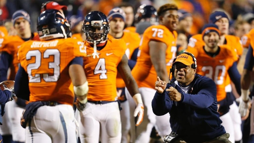 Virginia head coach Mike London, right, reacts to a touchdown by Virginia running back Khalek Shepherd (23) during the second half of an NCAA college football game against Miami in Charlottesville, Va., Saturday, Nov. 22, 2014. Virginia won the game 30-13. (AP Photo/Steve Helber)