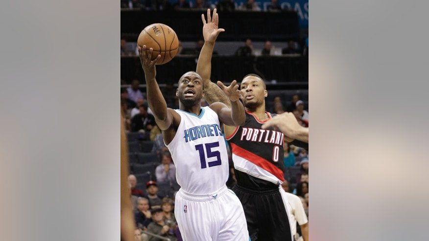Charlotte Hornets' Kemba Walker (15) drives past Portland Trail Blazers' Damian Lillard (0) during the first half of an NBA basketball game in Charlotte, N.C., Wednesday, Nov. 26, 2014. (AP Photo/Chuck Burton)