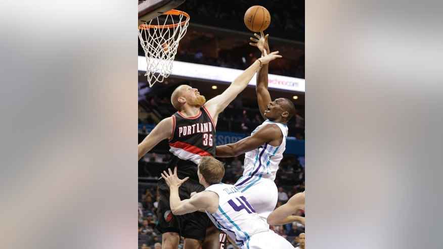 Charlotte Hornets' Bismack Biyombo, right, shoots over Portland Trail Blazers' Chris Kaman, left, during the first half of an NBA basketball game in Charlotte, N.C., Wednesday, Nov. 26, 2014. (AP Photo/Chuck Burton)