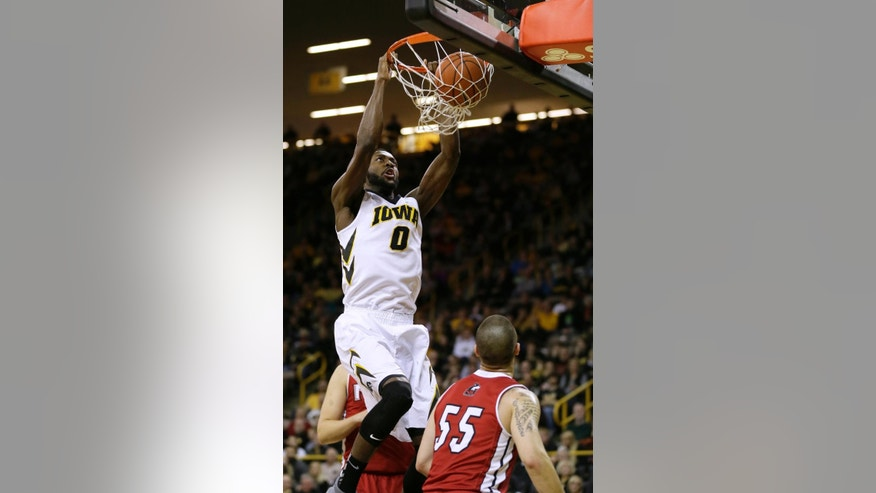 Iowa center Gabriel Olaseni (0) dunks the ball over Northern Illinois guard Michael Orris (55) during the first half of an NCAA college basketball game, Wednesday, Nov. 26, 2014, in Iowa City, Iowa. (AP Photo/Charlie Neibergall)
