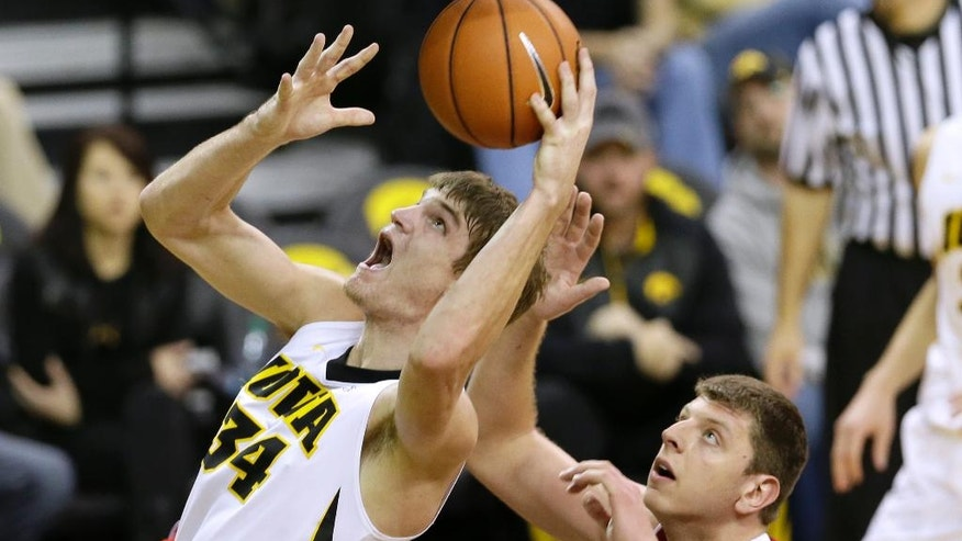 Iowa center Adam Woodbury, left, shoots over Northern Illinois center Jordan Threloff, right, during the second half of an NCAA college basketball game, Wednesday, Nov. 26, 2014, in Iowa City, Iowa. (AP Photo/Charlie Neibergall)