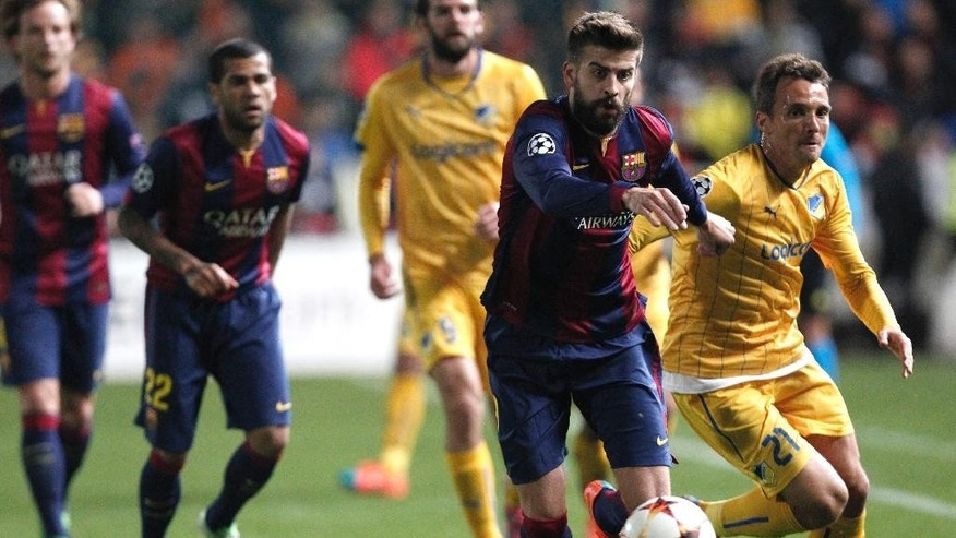 Barcelona's Gerard Pique fights for the ball with APOEL's Gustavo Manduca during a Champions League Group F soccer match between APOEL and FC Barcelona at GSP stadium, in Nicosia, Cyprus, Tuesday, Nov. 25, 2014. (AP Photo/Petros Karadjias)