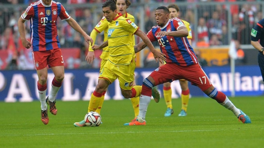 Bayern's Jerome Boateng, right, Xabi Alonso, left,  and Hoffenheim's Roberto Firmino from Brazil, center,  challenge for the ball during the Bundesliga  soccer match between FC Bayern Munich and 1899 Hoffenheim in the Allianz Arena in Munich, Germany, on Saturday, Nov. 22, 2014. (AP Photo/Kerstin Joensson)