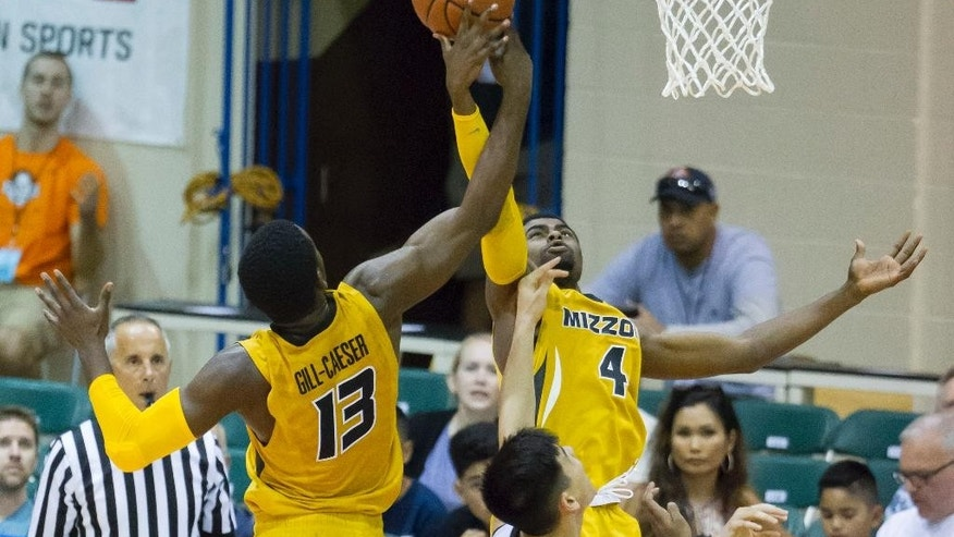 Missouri guards Montaque Gill-Caesar (13) and Tramaine Isabell (4) work to control a rebound while playing against Chaminade in the second half of an NCAA college basketball game at the Maui Invitational on Wednesday, Nov. 26, 2014, in Lahaina, Hawaii. Missouri won 74-60. (AP Photo/Eugene Tanner) (AP Photo/Eugene Tanner)