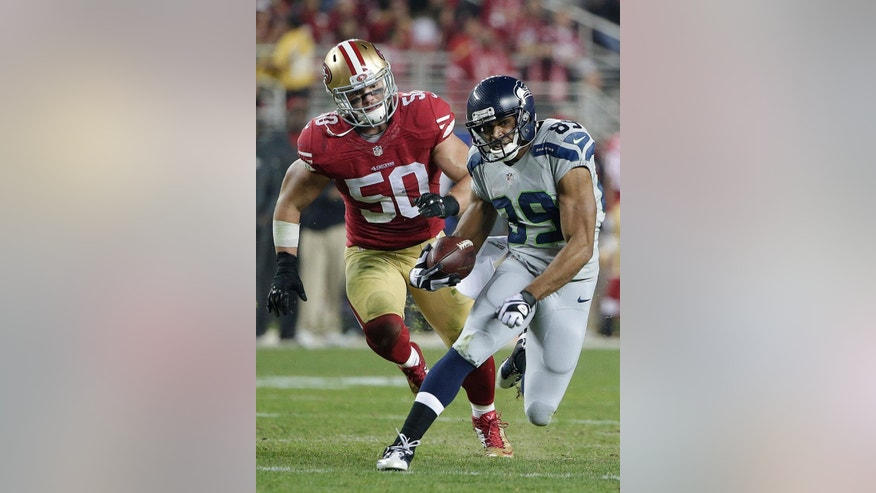 Seattle Seahawks wide receiver Doug Baldwin (89) runs from San Francisco 49ers inside linebacker Chris Borland (50) during the first quarter of an NFL football game in Santa Clara, Calif., Thursday, Nov. 27, 2014. (AP Photo/Marcio Jose Sanchez)