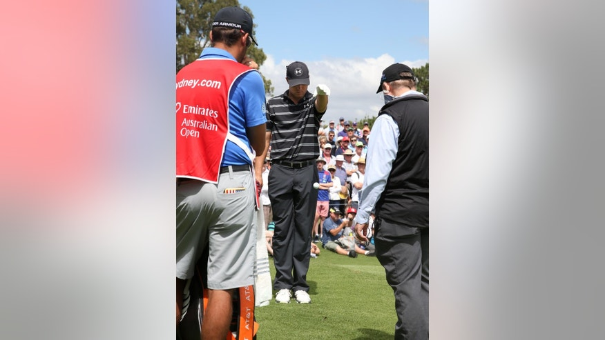 Jordan Spieth, center, of the U.S. takes a drop as an official, right, observes after a marshal disturbed Spieth's ball on the 4th hole during the second round of the Australian Open Golf championship in Sydney, Friday, Nov. 28, 2014. (AP Photo/Rick Rycroft)