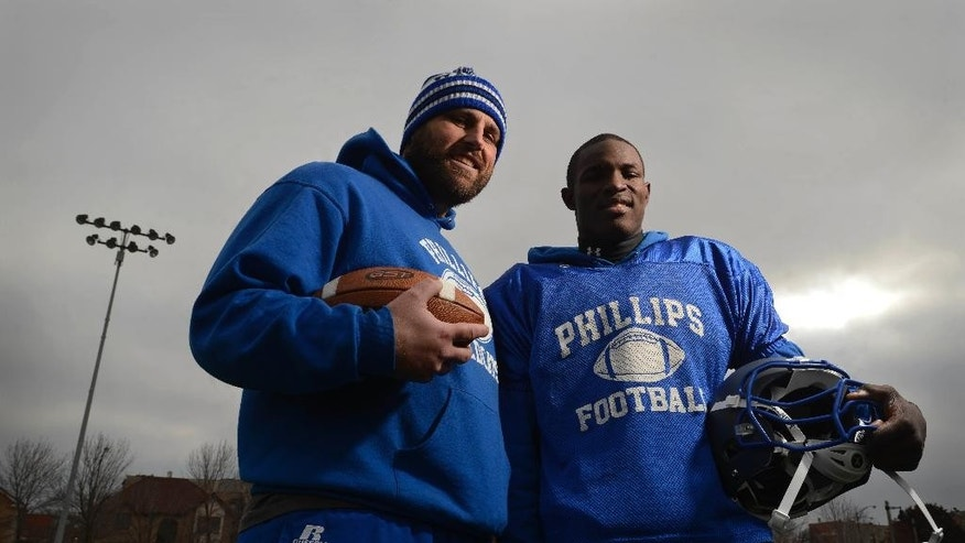 "In this Nov. 26, 2014 photo, Phillips Academy assistant coach Michael Larson left, poses with Phillips Academy player Jamal Brown, 19, at their practiced field in the south side Chicago. ""Football isn't as hard as our everyday lives,"" said Brown, a former dropout and gangbanger who now lives with Larson and is headed to college on a football scholarship. (AP Photo/ Paul Beaty)"