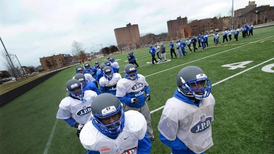 In this Nov. 26, 2014 photo, Phillips Academy players warm up during practice on the south side of Chicago. Unlike the powerhouses that normally play for high school football championships, the Phillips Academy Wildcats must lug their helmets and pads to a city park to practice. They have no field of their own. (AP Photo/ Paul Beaty)