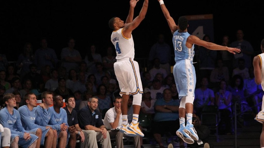 UCLA's Norman Powell (4) takes a shot against UNC's J.P. Tokoto (13) during their game in the Battle 4 Atlantis basketball tournament in Paradise Island, Bahamas, Thursday Nov. 27, 2014. (AP Photo/Tim Aylen)