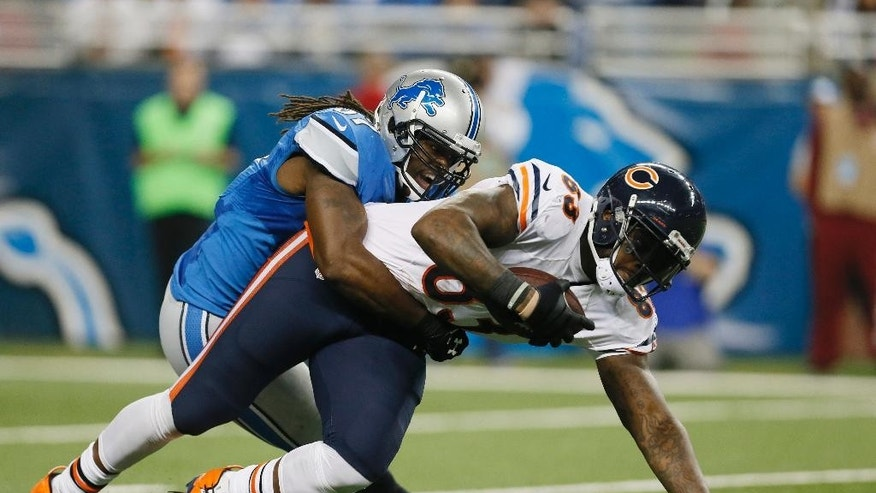 Chicago Bears tight end Martellus Bennett (83) is stopped by Detroit Lions linebacker Josh Bynes (57) during the second half of an NFL football game in Detroit, Thursday, Nov. 27, 2014. (AP Photo/Paul Sancya)