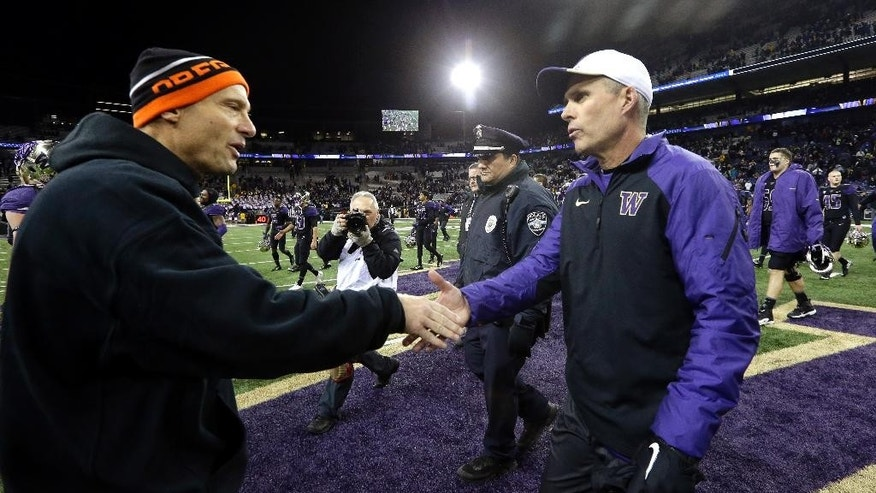 Washington head coach Chris Petersen, right, and Oregon State head coach Mike Riley meet  after an NCAA college football game Saturday, Nov. 22, 2014, in Seattle. Washington won 37-13. (AP Photo/Elaine Thompson)