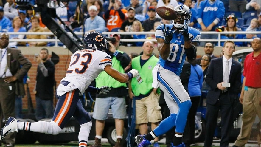 Detroit Lions wide receiver Calvin Johnson (81), defended by Chicago Bears cornerback Kyle Fuller (23), pulls in a 6-yard pass for a touchdown during the first half of an NFL football game in Detroit, Thursday, Nov. 27, 2014. (AP Photo/Rick Osentoski)