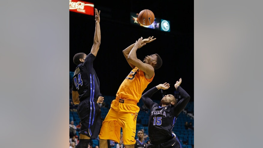 Oklahoma State's Leyton Hammonds, center, shoots between Tulsa's Brandon Swannegan, left, and Marquel Curtis during the first half of an NCAA college basketball game Wednesday, Nov. 26, 2014, in Las Vegas. (AP Photo/John Locher)