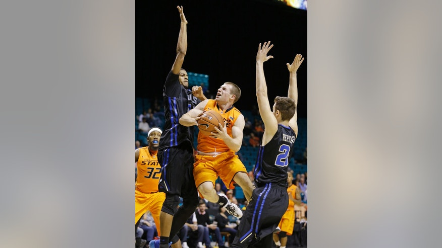 Oklahoma State guard Phil Forte III, center, goes up for a shot against Tulsa forward Brandon Swannegan, left, and guard Stevie Repichowski during the first half of an NCAA college basketball game Wednesday, Nov. 26, 2014, in Las Vegas. (AP Photo/John Locher)
