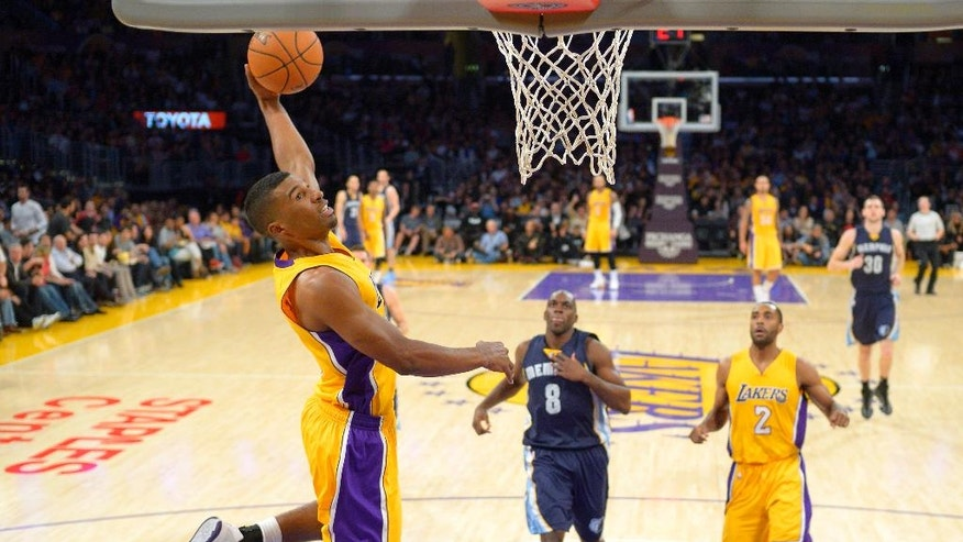 Los Angeles Lakers guard Ronnie Price, left, dunks as Memphis Grizzlies guard Quincy Pondexter, center, looks on along with Lakers guard Wayne Ellington during the first half of an NBA basketball game, Wednesday, Nov. 26, 2014, in Los Angeles. (AP Photo/Mark J. Terrill)