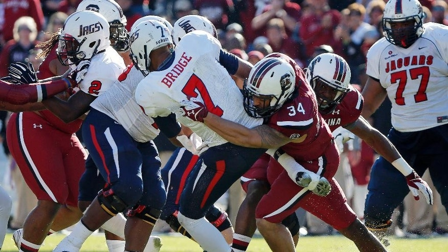 South Alabama quarterback Brandon Bridge (7) fumbles the ball while being tackled by South Carolina defensive end Mason Harris (34) during the second half of an NCAA college football game in Columbia, S.C., Saturday, Nov. 22, 2014. South Carolina beat South Alabama  37-12. (AP Photo/Stephen B. Morton)