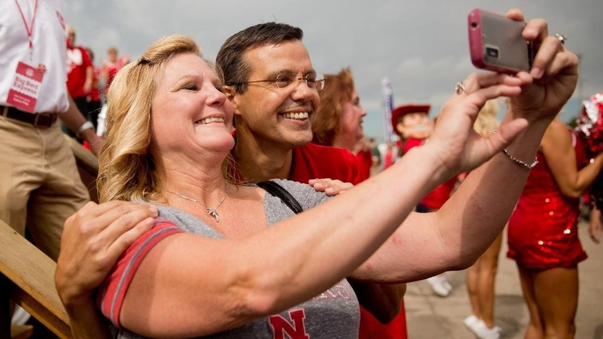 FILE - In this June 28, 2014, file photo, Terri Jasa, left, takes a selfie with Nebraska men's basketball head coach Tim Miles in Columbus, Neb. . (AP Photo/The Omaha World-Herald, Sarah Hoffman) MAGS OUT; ALL NEBRASKA LOCAL BROADCAST TV OUT