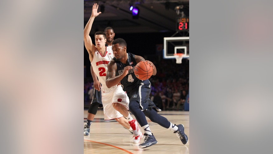 Georgetown's D'Vauntes Smith-Rivera (4) hustles to get away from Wisconsin's Bronson Koenig (24) their game in the Battle 4 Atlantis basketball tournament in Paradise Island, Bahamas, Thursday Nov. 27, 2014. (AP Photo/Tim Aylen)